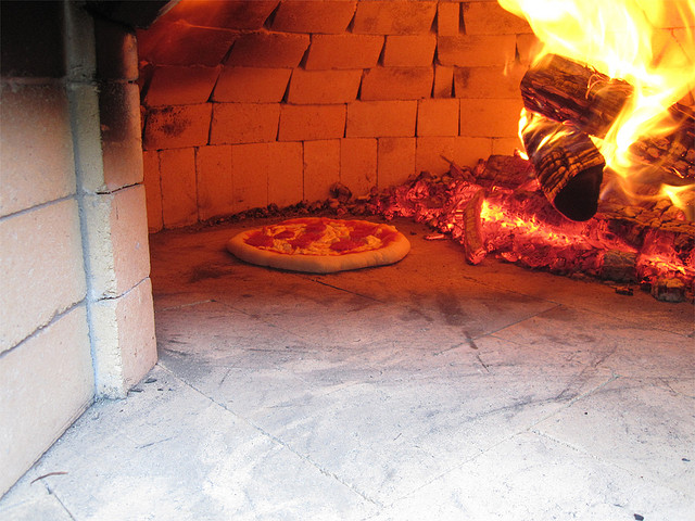 Pizza cooking in the hot stone oven
