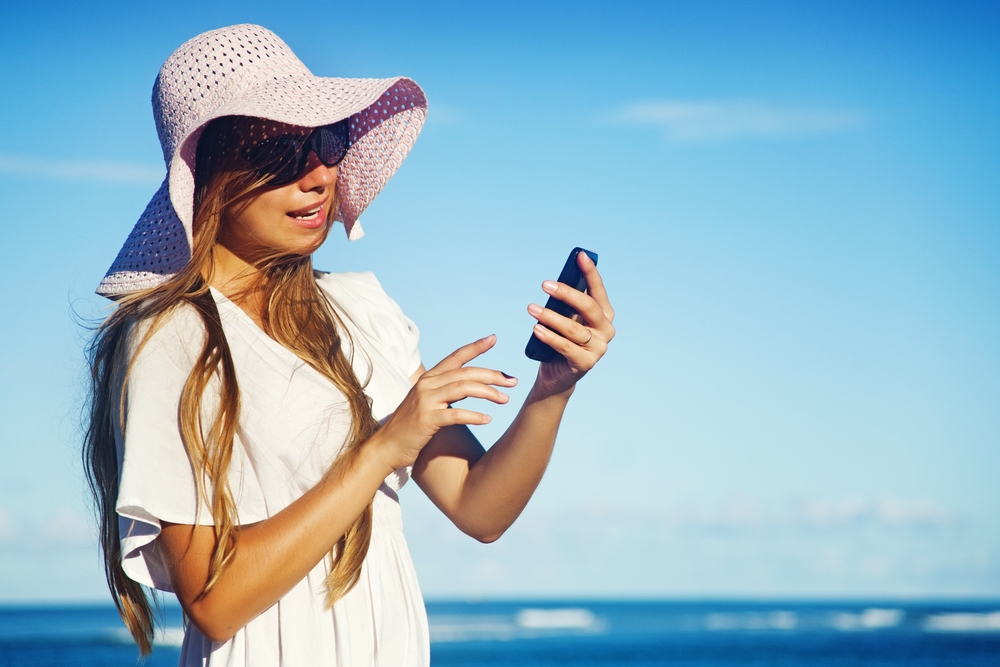 Woman with a floppy hat and phone