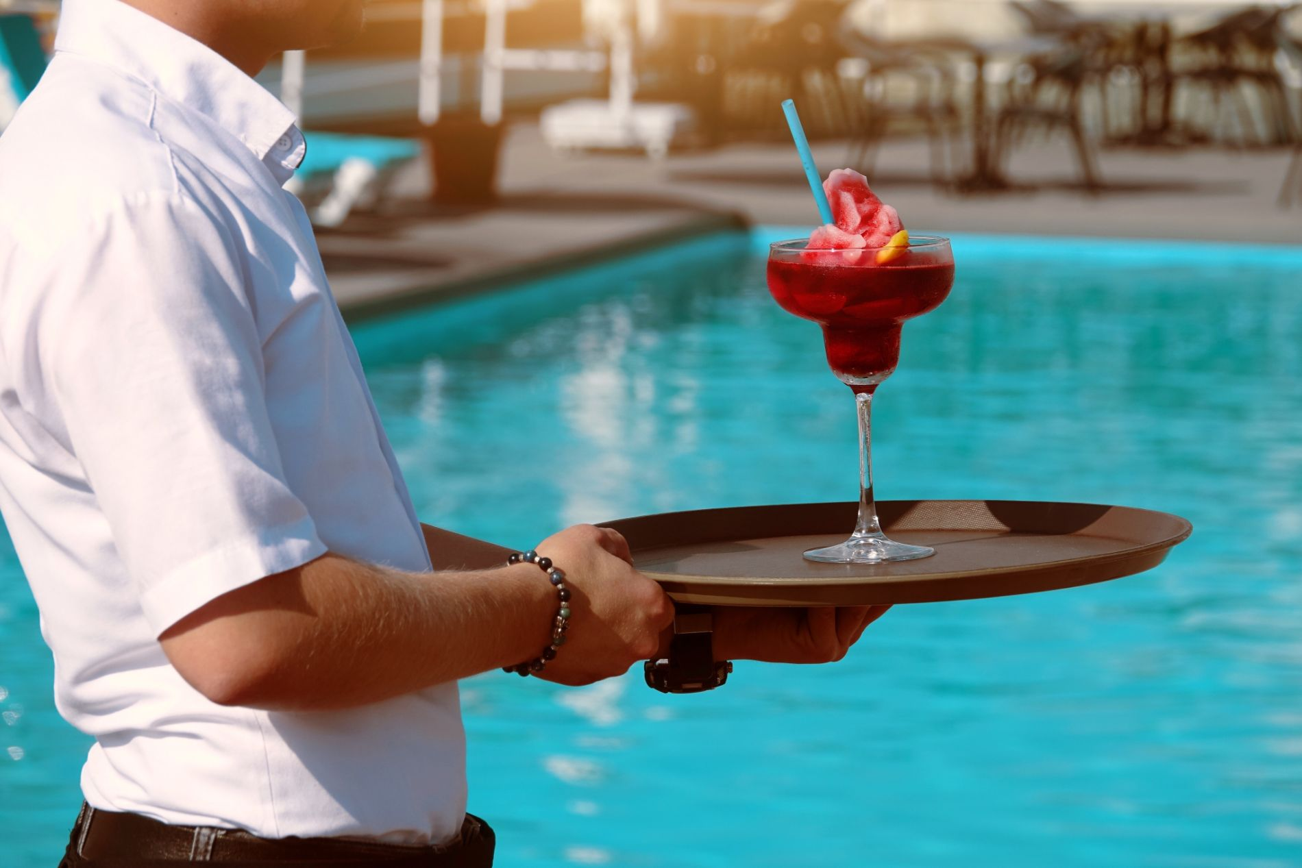 Waiter serving Bright Cocktail by Swimming Pool
