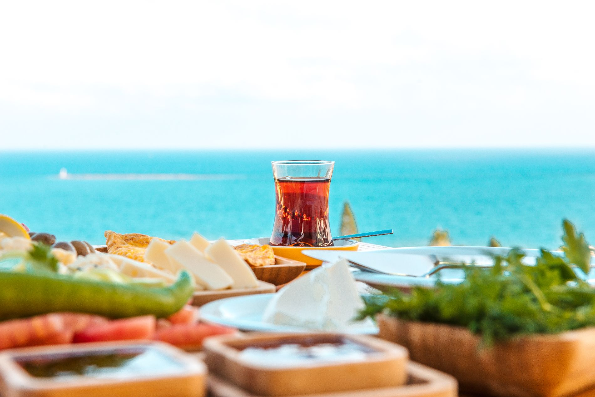 Turkish tea with breakfast on the table in front of sea background landscape