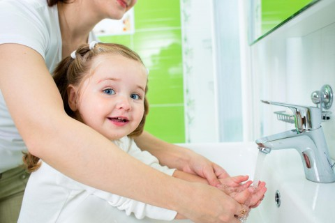 Mother washing kids hands