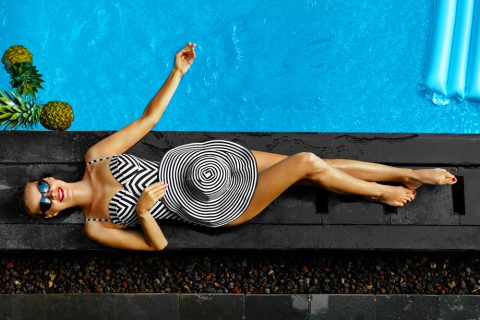 Lady laying poolside with fancy swimsuit