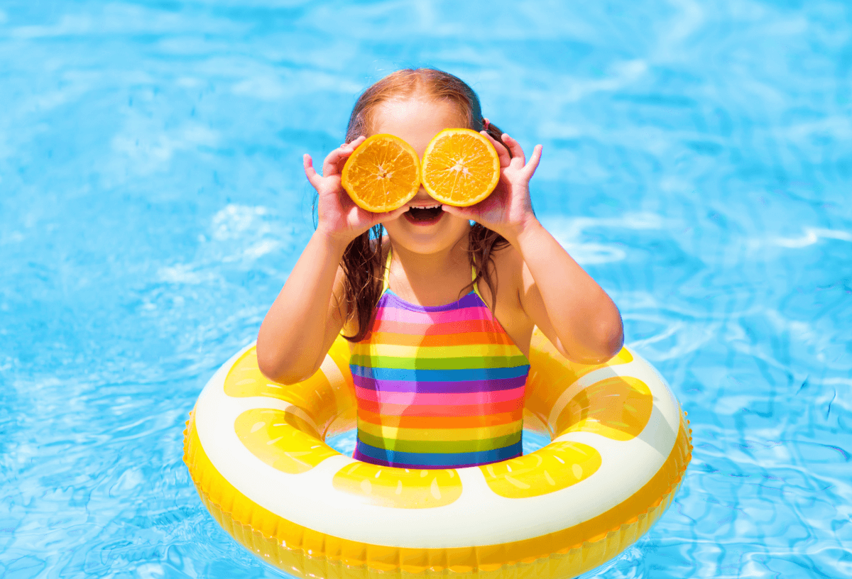 Child having fun on holiday in the pool with orange segments covering her eyes