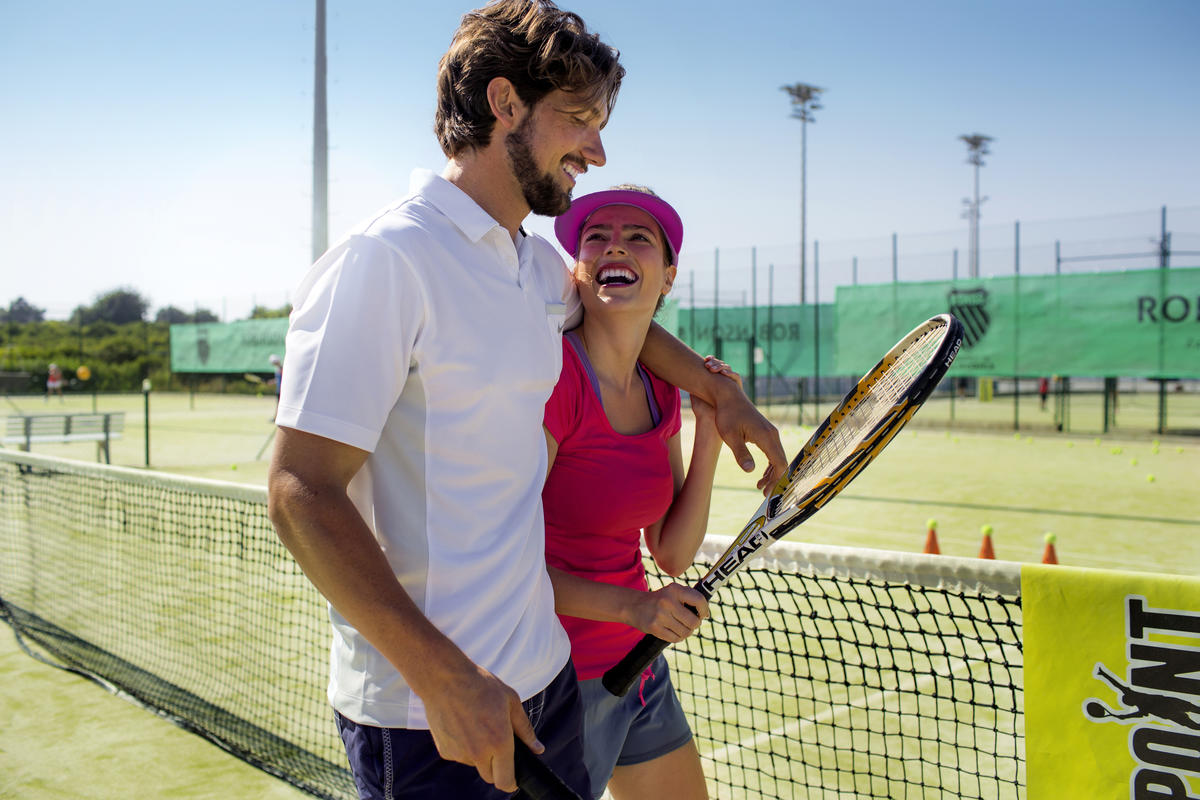 Happy couple playing tennis