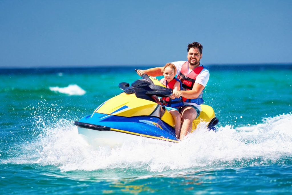 happy, excited family, father and child having fun on jet ski