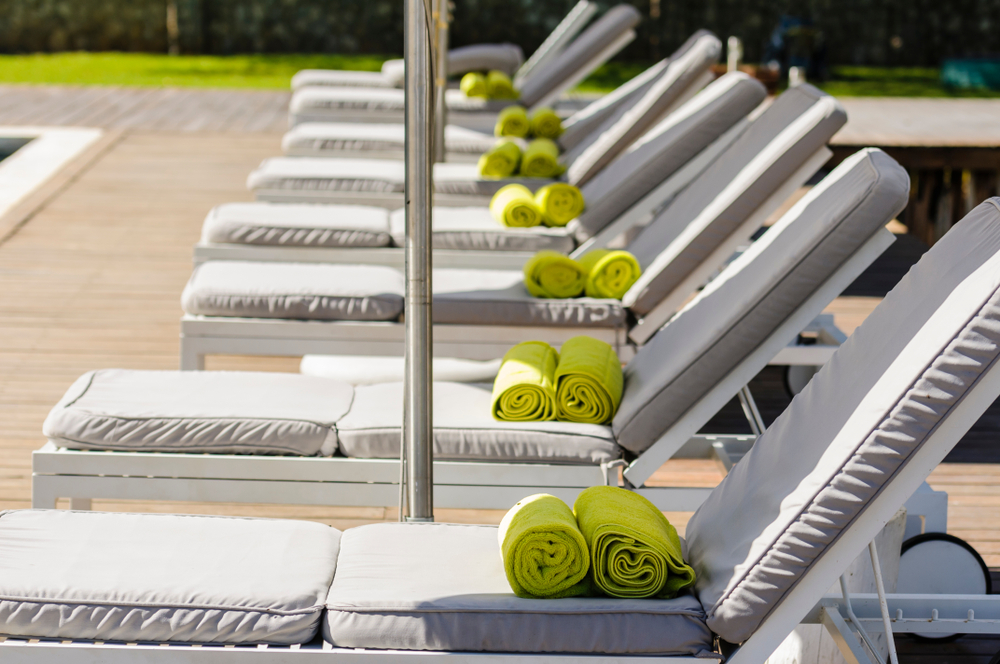 Green towels on a row of empty sunloungers beside a swimming pool