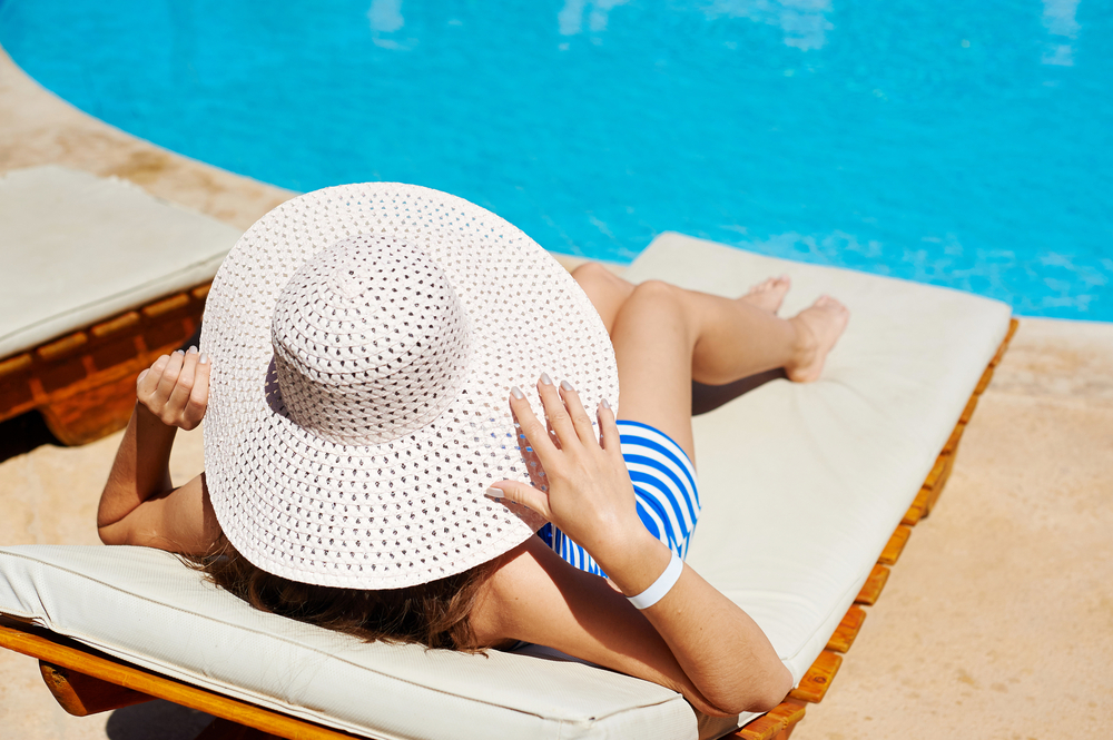 woman in a big white hat on a lounger by the pool
