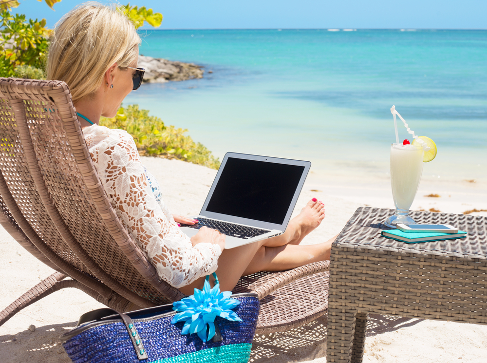 Women using laptop whilst sitting by the beach
