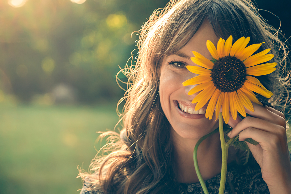 Girl hiding half of face behind sunflower whilst smiling